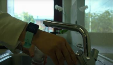 Hands filling up a glass of water from a kitchen tap