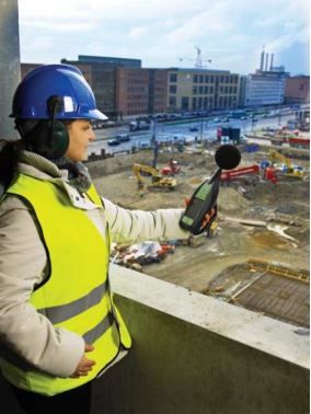 Woman monitoring sound levels at building site