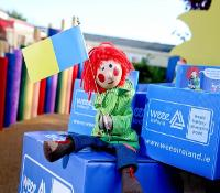 Image of Irish puppet Bosco sitting on WEEE battery recycling boxes