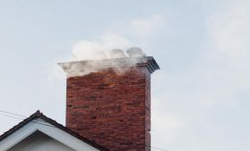 Smoke coming from the chimney of a home